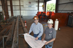 San Jacinto College graduate Jim Hodges, left, looks over construction project plans with Archie Devault, shop superintendent for Total Industrial Services. Photo credit: Rob Vanya